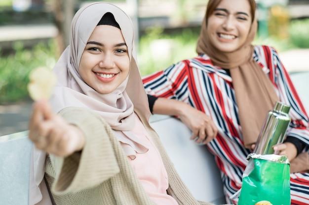 친구와 함께 행복 한 이슬람 젊은 여자는 공원에서 휴식을 취하는 동안 간식을 즐길 수