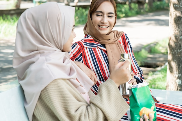 Happy muslim young woman with friend enjoy their snack while relaxing in the park