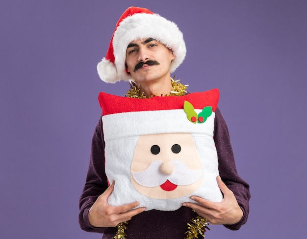 Felice uomo baffuto che indossa un cappello da babbo natale con orpelli intorno al collo che tiene un cuscino di natale con un sorriso sul viso in piedi sul muro viola