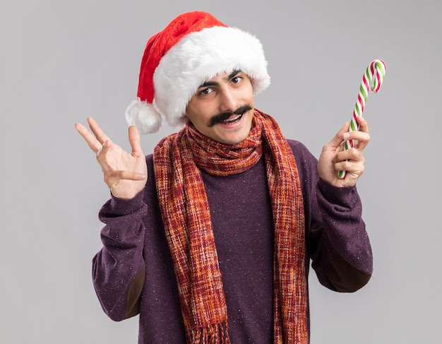 흰색 벽 위에 유쾌하게 서있는 사탕 지팡이를 들고 그의 목에 따뜻한 스카프와 함께 크리스마스 산타 모자를 쓰고 행복 콧수염 남자