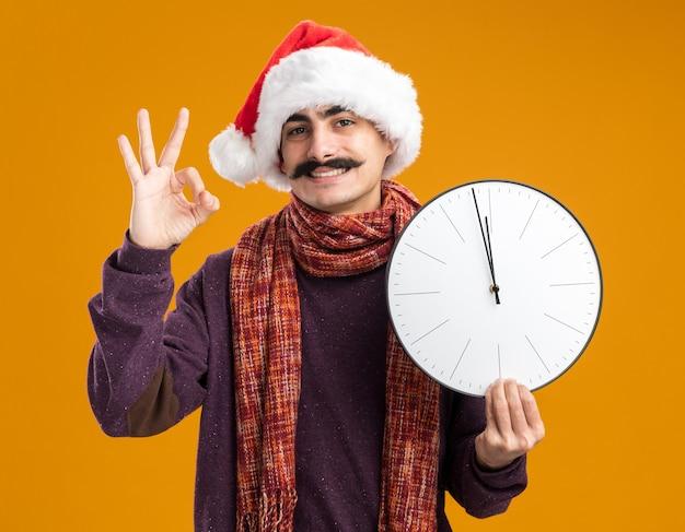Felice baffuto uomo che indossa il cappello di babbo natale con sciarpa calda intorno al collo tenendo l'orologio sorridente mostrando segno ok in piedi su sfondo arancione