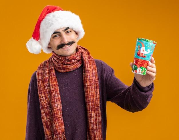 오렌지 배경 위에 서있는 얼굴에 미소로 카메라를보고 다채로운 종이 컵을 들고 그의 목에 따뜻한 스카프와 함께 크리스마스 산타 모자를 쓰고 행복 콧수염 남자