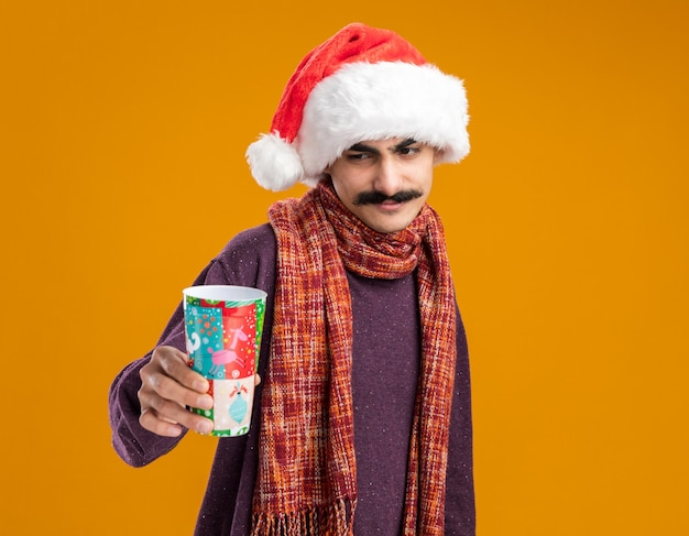 오렌지 배경 위에 서있는 얼굴에 미소로보고 다채로운 종이 컵을 들고 그의 목에 따뜻한 스카프와 함께 크리스마스 산타 모자를 쓰고 행복 콧수염 남자