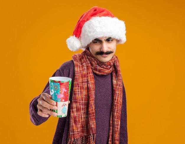 Felice baffuto uomo che indossa il natale santa hat con calda sciarpa intorno al collo tenendo colorato bicchiere di carta guardando con il sorriso sul viso in piedi su sfondo arancione