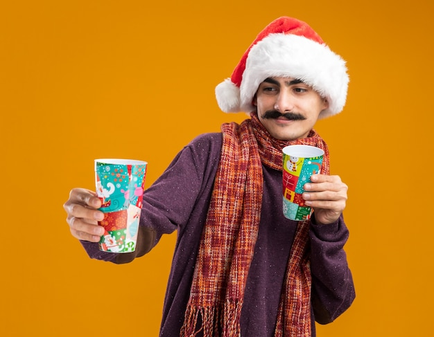 오렌지 배경 위에 서있는 얼굴에 미소로 그들을보고 다채로운 종이 컵을 들고 그의 목에 따뜻한 스카프와 함께 크리스마스 산타 모자를 쓰고 행복 콧수염 남자