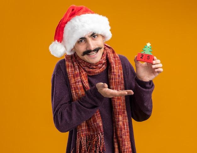 Счастливый усатый мужчина в новогодней шапке санта-клауса с теплым шарфом на шее, держащий игрушечные кубики с датой двадцать пять, представляя с рукой улыбаясь, стоя на оранжевом фоне