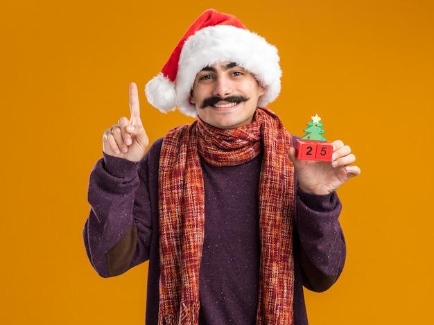 Счастливый усатый мужчина в рождественской шапке санта-клауса с теплым шарфом на шее держит игрушечные кубики с датой двадцать пять, весело улыбаясь, показывая указательный палец, стоящий на оранжевом фоне