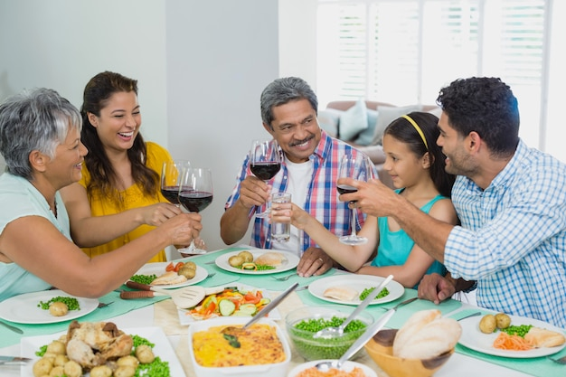 Happy mutigeneration family toasting a glasses of red wine while having meal