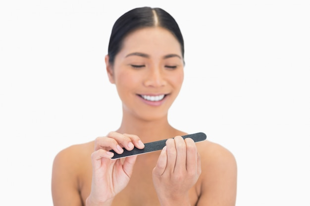Happy natural brunette using nail file