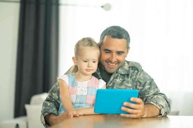 パパの近くで幸せ。パパの近くに座って、漫画を見て幸せを感じているかわいい金髪の娘