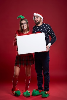Coppie felici del nerd in vestiti di natale che tengono documento in bianco
