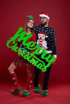 孤立したクリスマスの服で幸せなオタクカップル