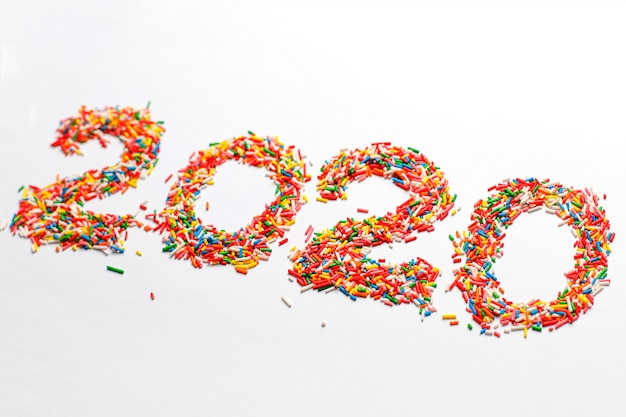 ハッピーニュー2020年。白で隔離される明るい虹砂糖振りかけるとカラフルな数字の形