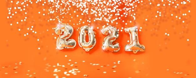 2021 년 새해 복 많이 받으세요. 휴일 헬륨 골드 금속 풍선 번호 및 오렌지 배경에 떨어지는 색종이