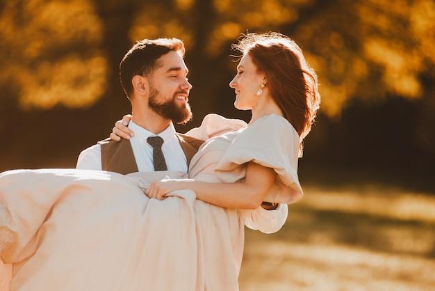 幸せな新しい家族、腕に花嫁を保持している新郎