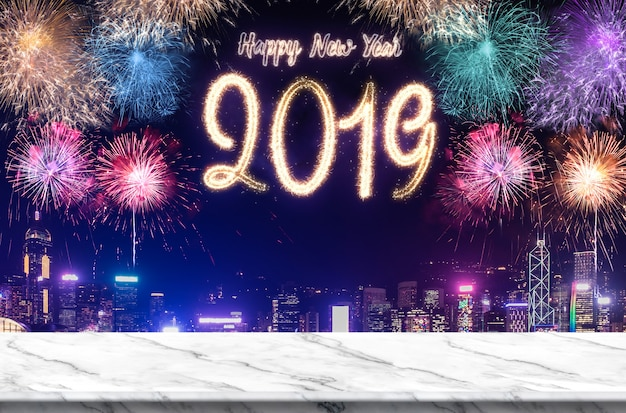 Happy new year 2019 fireworks over cityscape at night with empty white marlbe table