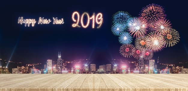 Happy new year 2019 fireworks over cityscape at night with empty wood plank table top