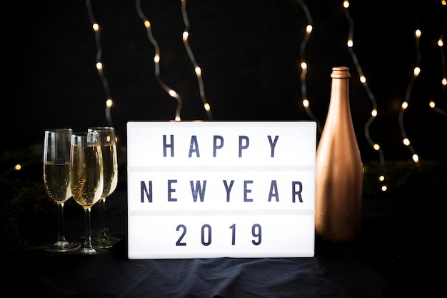 Happy new year 2019 inscription on board with bottle