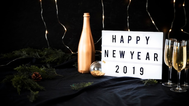 Happy new year 2019 inscription on board with glasses