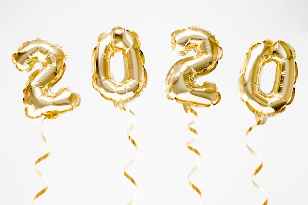 Happy new year 2020 celebration. gold foil balloons numeral 2020 hanging in the air on white background