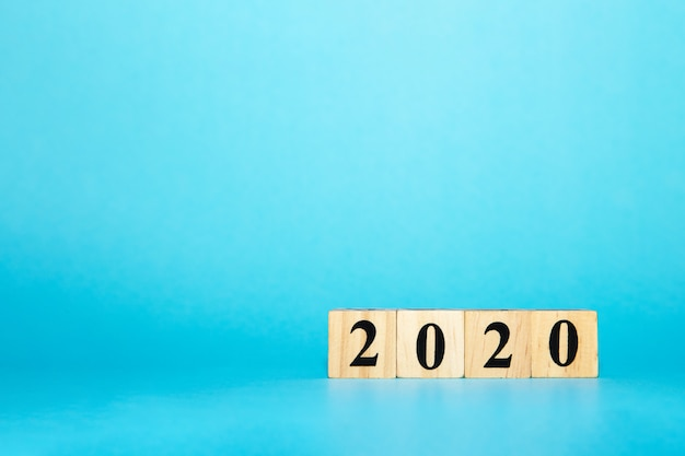 Happy new year 2020 concept with wooden block cube on blue