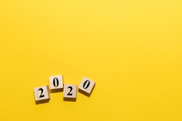 Happy new year 2020 concept with wooden block cube on yellow