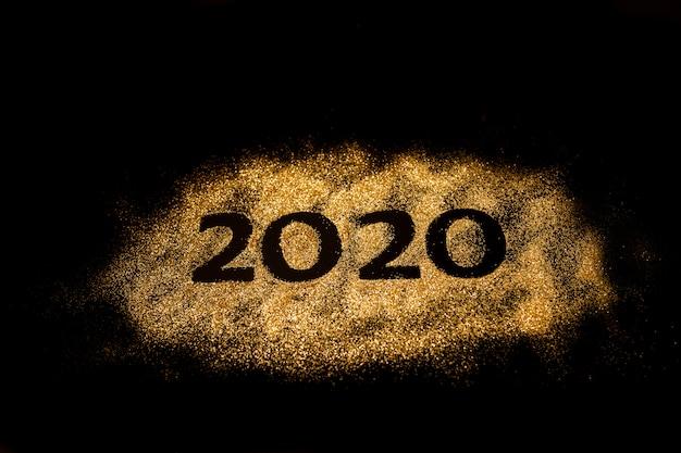 新年あけましておめでとうございます2020。数字2と0の創造的なコラージュは2020年を構成しました。デザインのための黒い背景に美しい輝くゴールデン番号2020。