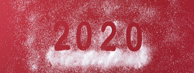Happy new year 2020 date with snowfall on red