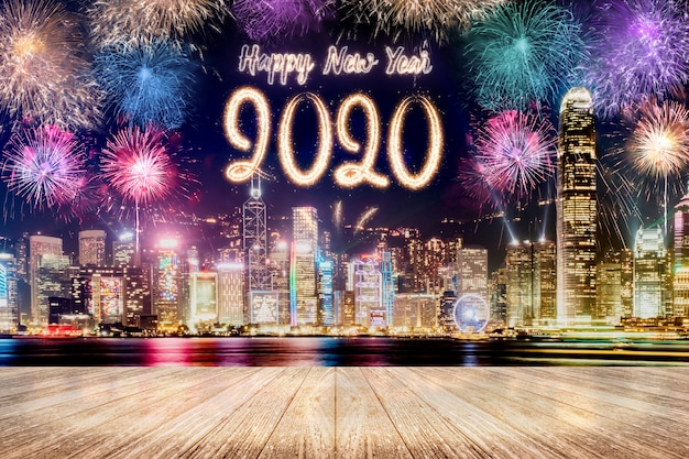Happy new year 2020 fireworks over cityscape at night with empty wood plank table