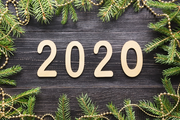Happy new year 2020. golden date, border of evergreen branches on black board. christmas . flat lay. top view. xmas.