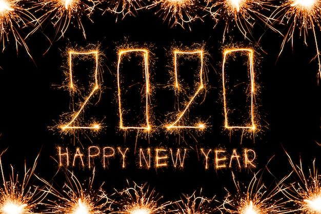 Happy new year 2020. креативный текст happy new year 2020, написанный искрящимися бенгальскими огнями
