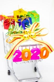 新年あけましておめでとうございます2020。白い背景の上のバスケットカートの番号2020とギフトボックスからのシンボル。