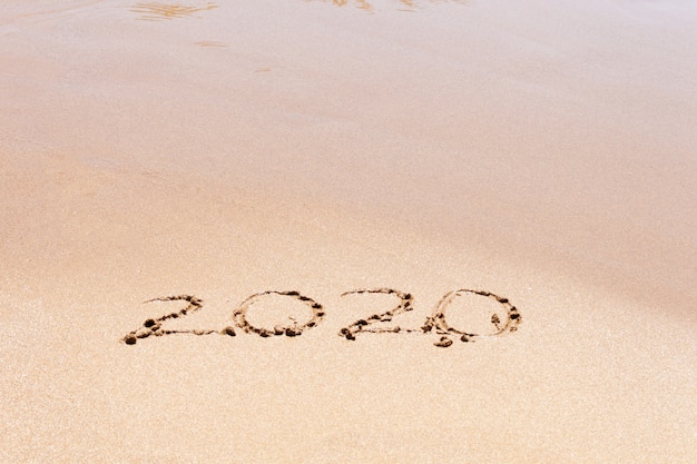 Happy new year 2020 text on the beach. planning vacation.