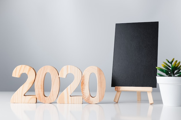 Happy new year 2020 with blackboard on white table and grey