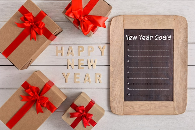 Happy new year 2020 wood and new year's goals list written on chalkboard with gift box