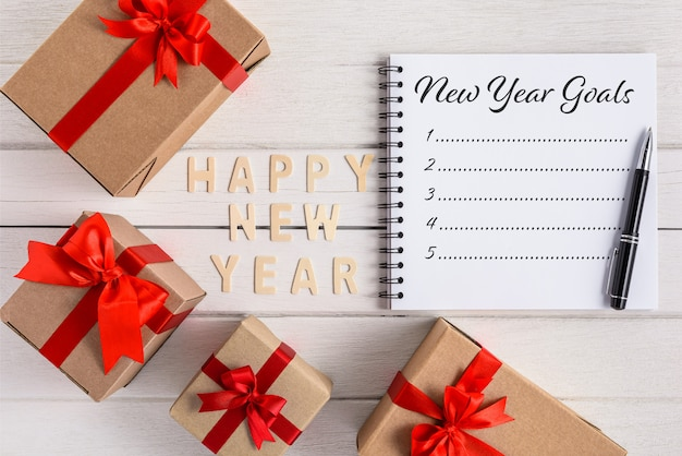 Happy new year 2020 wood and new year's goals list written on notebook with gift box