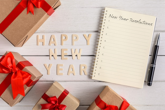 Happy new year 2020 wood and new year's resolutions list written on notebook with gift box