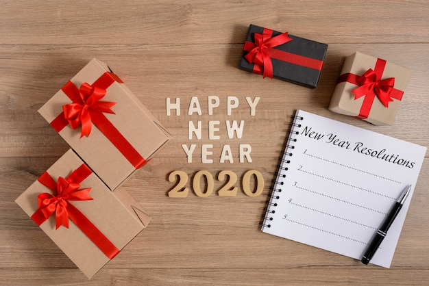 Happy new year 2020 wood and new year's resolutions list written