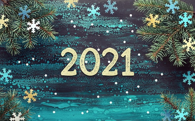 Happy new year 2021 background with fir twigs, yellow, blue and turquoise paper snowflakes.