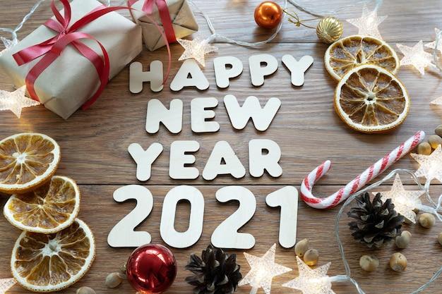 明けましておめでとうございます2021年。クリスマス作曲。暗い木製のテーブルの新年のレイアウト。コーン、おもちゃ、ギフト、花輪。