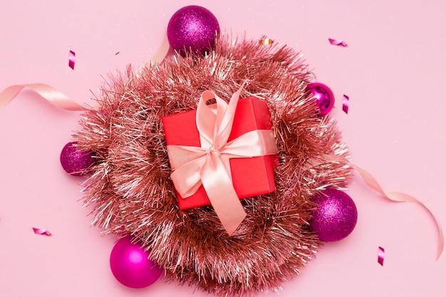 明けましておめでとうございます2021年。ピンクの背景にクリスマスのおもちゃ、ギフトボックス、赤い帽子。クリスマス。
