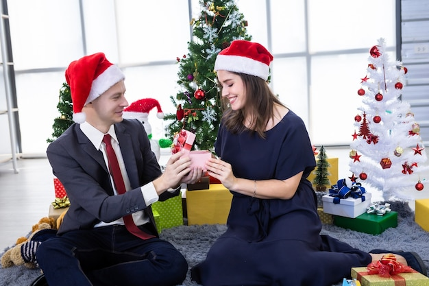 明けましておめでとうございます2021年のコンセプト。贈り物を交換し、クリスマスと大晦日のパーティーでプレゼントを贈る幸せなカップルクリスマスツリーの背景