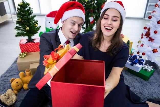 明けましておめでとうございます2021年のコンセプト。贈り物を交換し、クリスマスと大晦日のパーティーでプレゼントを贈る幸せなカップル