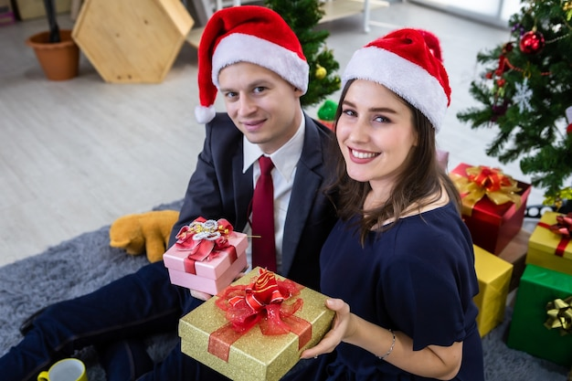 Happy new year 2021 concept. happy couple holding exchanging gifts and give a present in christmas and new year's eve party christmas tree background