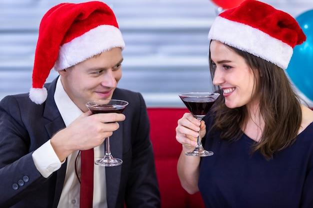 明けましておめでとうございます2021年のコンセプト。クリスマスと大晦日のパーティーでチャリンというシャンパンのグラスを持って幸せなカップル