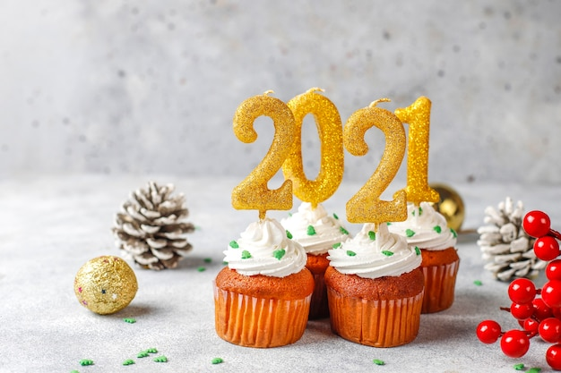 Happy new year 2021, cupcakes with golden candles.