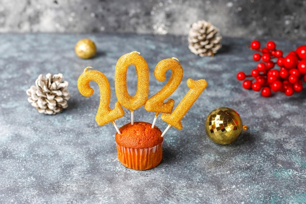 Happy new year 2021,cupcakes with golden candles.