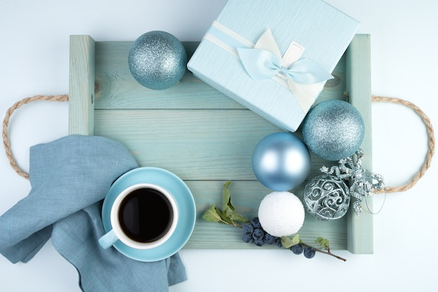 Happy new year 2021, festive composition with a cup of coffee, gift box, christmas balloons and a tray in a soft blue color