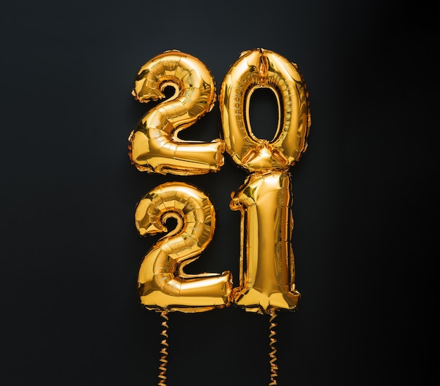 Happy new year 2021 gold air balloon text with ribbons on black.