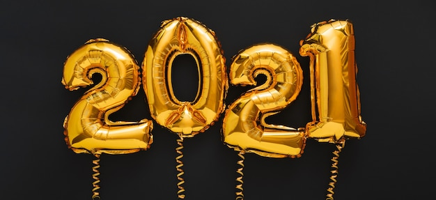 Happy new year 2021 gold air balloons text with ribbons on black long banner.